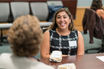 Female student smiles as she interacts with mentor at Paul College mentoring event