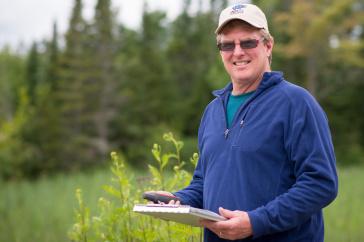UNH professor Pete Pekins in a meadow