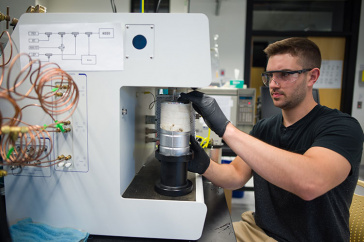 UNH student Christopher Bales '18 conducting chemical engineering research