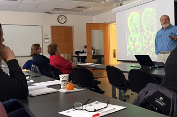 an instructor shows a colorful biology slide at the front of a classroom