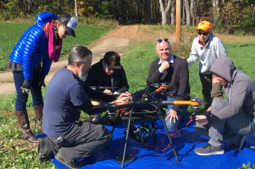 Group of researchers gathers around large drone outside on a sunny day.