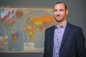 Associate Professor of Finance Milhail Miletkov standing in front of a world map