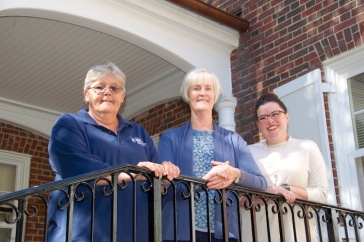 Penny Watson, Karen Gilbert, Jessica Willis on steps behind Hood House