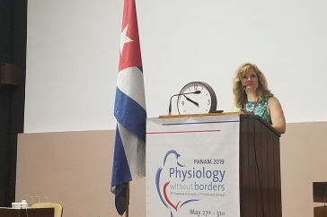 Associate professor of biological sciences and biotechnology Patricia Halpin chairing symposium in Havana, Cuba
