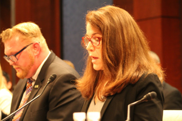 Sharyn Potter testifying before Congress with male in background