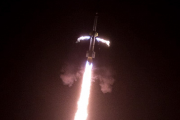 A rocket takes off with white-red flames behind it.