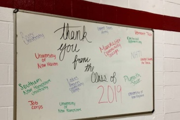 A whiteboard with various colleges and university names written on it