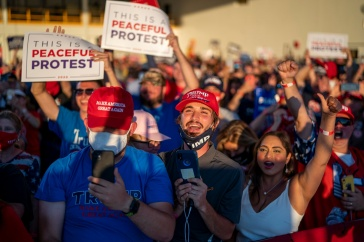 A group of people wearing Trump 2020 gear at a Trump rally.