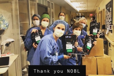 Emergency room workers at Tufts Medical Center holding bags of iced NOBL coffee