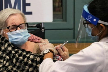 Photo of elderly woman receiving the COVID-19 vaccination