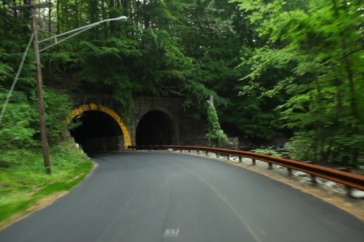 Roadway in rural America going beneath a tunnel.