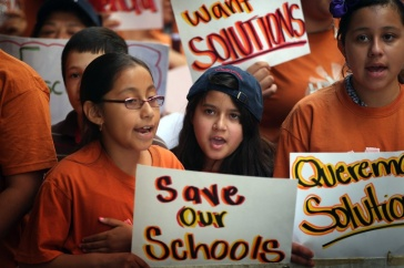 Grade school students wear orange shirts and hold protest signs.
