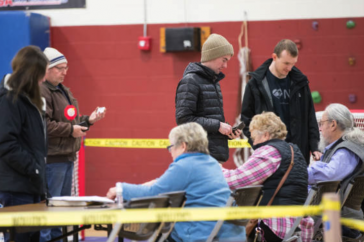 New Hampshire residents wait in line at a polling location