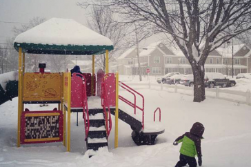 A young child plays on a playground covered in snow.