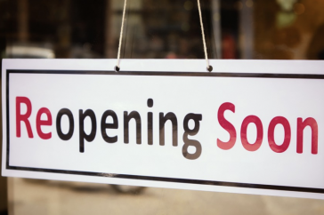 "Picture of a sign hanging on a door that says ""reopening soon"""