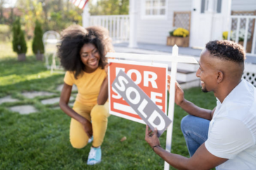 """A couple places a """"sold"""" sign  on top of a """"for sale"""" sign in their lawn."""
