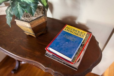 Photo showing an alcoholics anonymous handbook on a table.