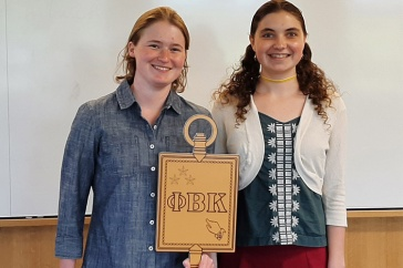 two students holding golden key