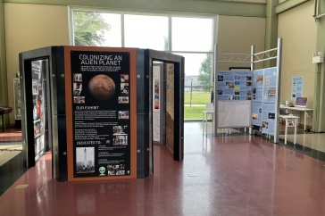 Two exhibits featuring posters and computer kiosks at a museum.