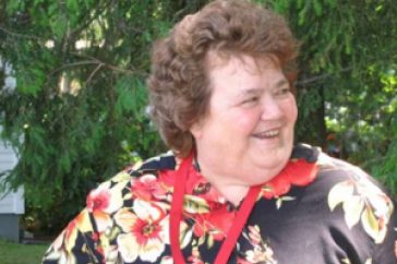 Marian West wearing a red and black floral shirt while standing outside in front of a tree.