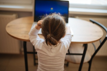 Photo of a young child working on a computer and seated at a table.