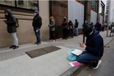 Men and women wait in line at an unemployment center