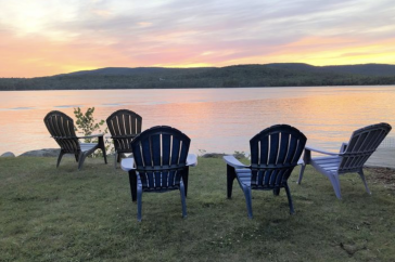 Adirondack chairs sit in front of a lake in Maine