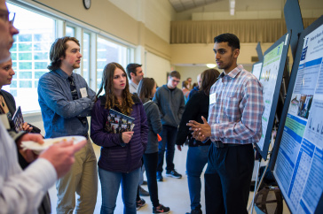 A male UNH student presents his research findings during the 2018 UNH Undergraduate Research Conference
