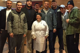 UNH football players with UNH chef on Thanksgiving