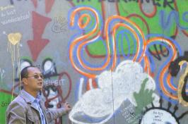 Ben Cariens stands in front of the replica Berlin Wall in Murkland Courtyard.