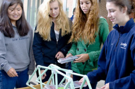 civil engineering students with paper bridge
