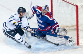 men's ice hockey player at goal against competing team