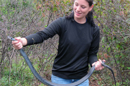 student with black racer snake