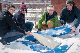 students and researchers measuring rooftop snow