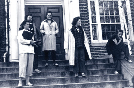 Female students outside academic building in blue jeans (dungarees)