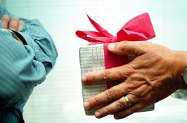 a person handing a gift to someone else who has their arms crossed