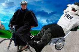 Professor riding a bike dressed for graduation, pulling Gnarlz in a trailer