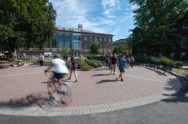 UNH students walking and biking through DeMeritt Courtyard