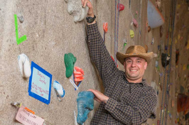 UNH graduate Bill Cudmor on climbing wall