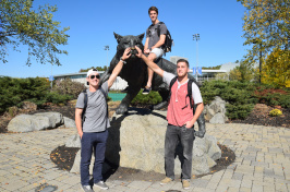 Three UNH students pose in front of the Wildcat statue.