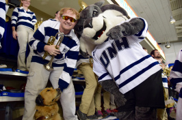 Travis Nevins '17 poses with his guide dog Mathis at a UNH hockey game.