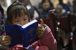 a chinese girl reading the Bible (EPA/How Hwee Young)