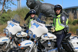 UNH police with their motorcycles in front of the wildcat statue
