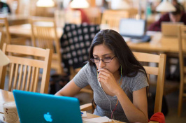 UNH student at her computer in Dimond Library