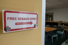 """Free Speech Zone"" sign next to a doorway"