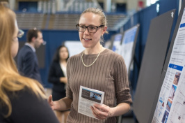 Graduate student Allison Leach in front of a research poster