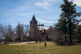 a student catching a frisbee in front of UNH's Thompson Hall
