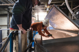 Smuttynose brewer Hannah Johnson '12 reaching into a brewing container