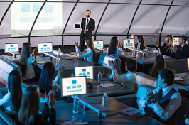 a man giving a presentation to a group of people at computers