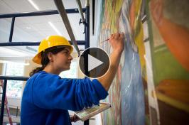 UNH art history graduate Corinne Long '12 restoring a mural in Hamilton Smith Hall at UNH